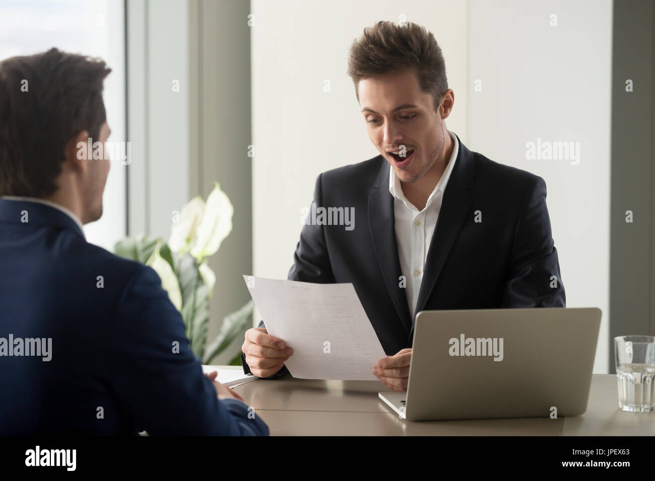 Excited businessman looking amazed while reading document, impre - Stock Image