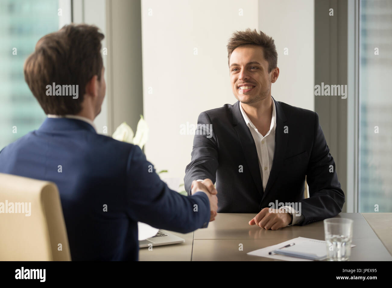 Two cheerful businessmen shaking hands, starting job interview o - Stock Image