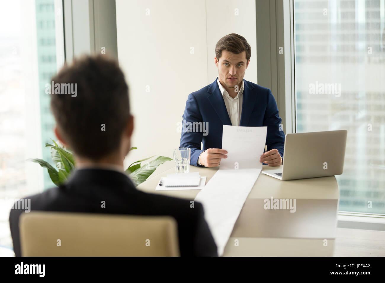 Surprised employer holding long resume, amazed with impressive c - Stock Image