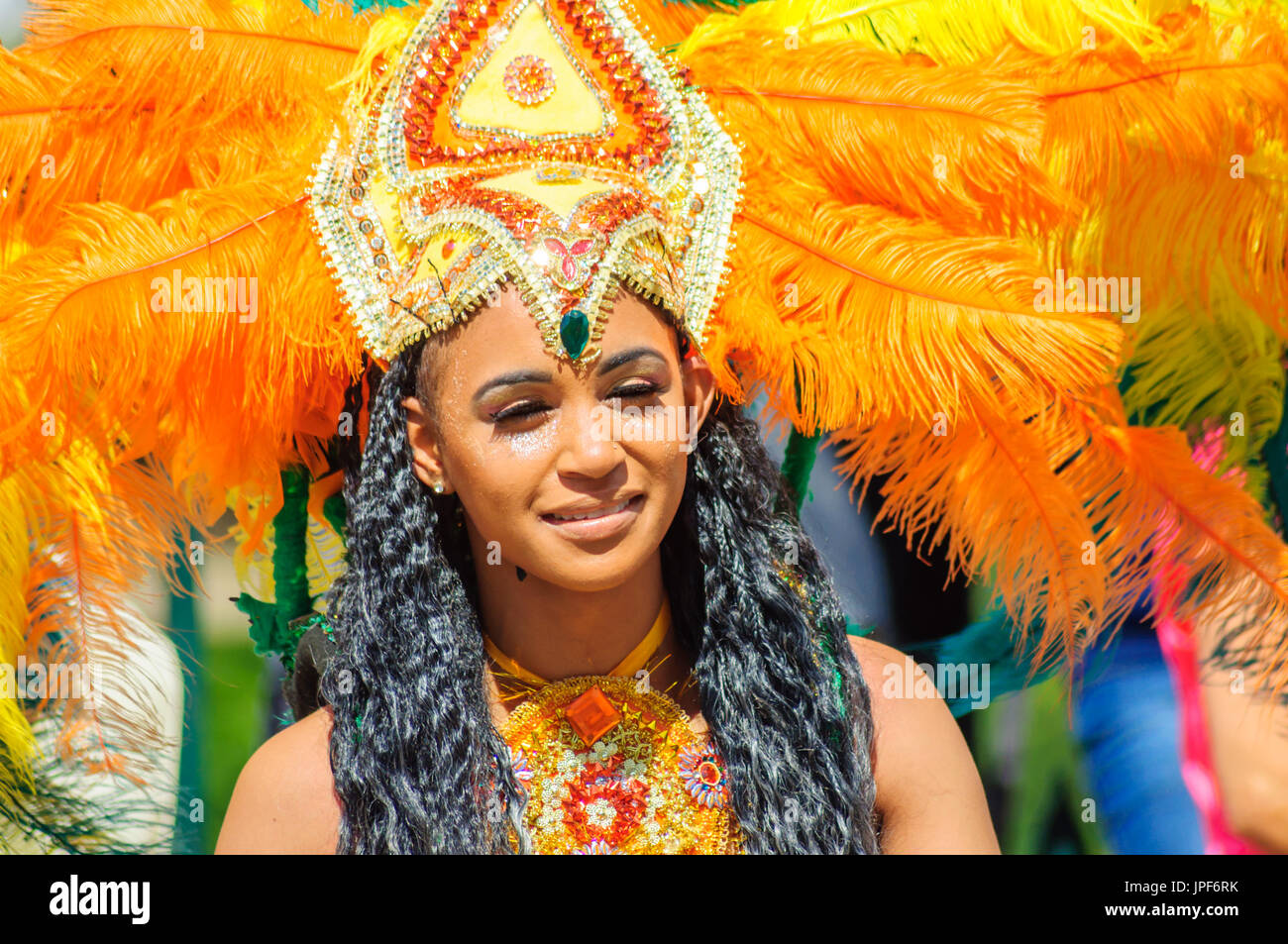 Female performer wearing a colorful costume and headdress in the parade on the streets of Edinburgh in the Carnival of The Jazz and Blues Festival - Stock Image