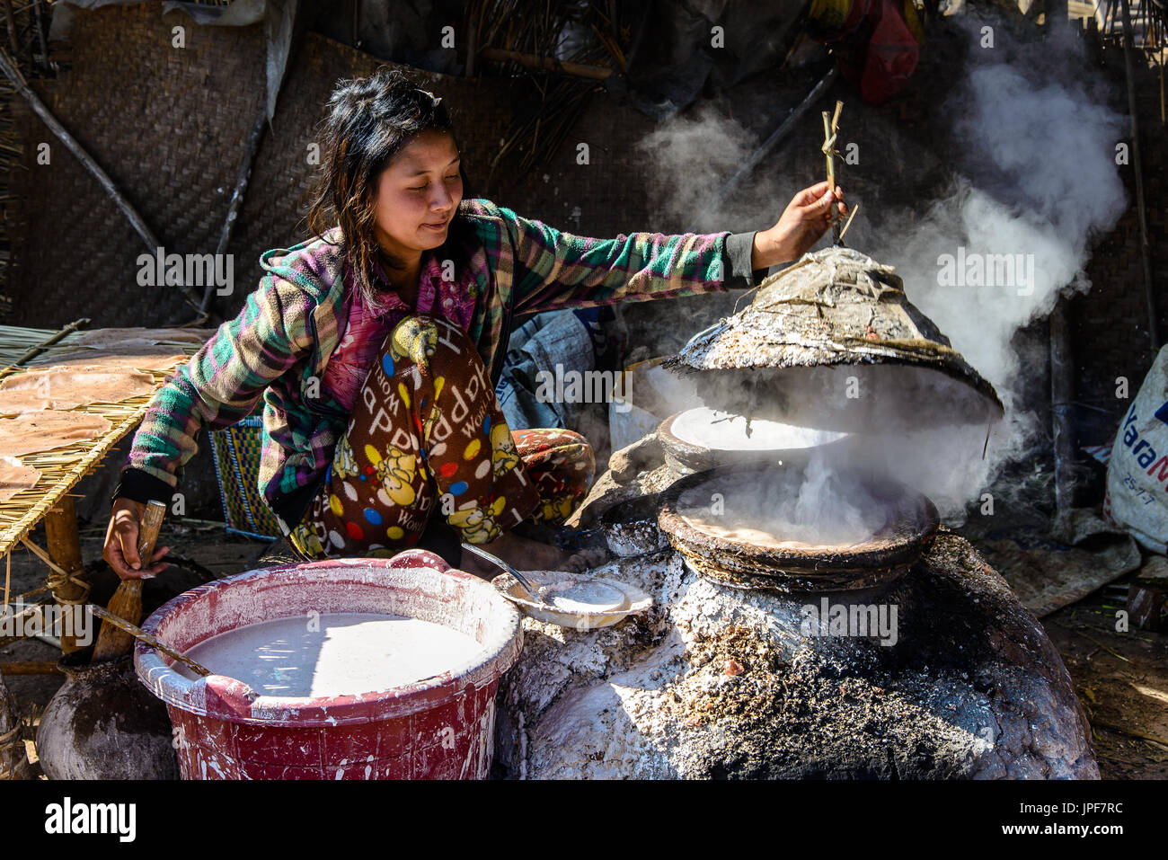 INLE LAKE, MYANMAR - FEBRUARY 15, 2014: young burmese lady cooking rice bred Stock Photo