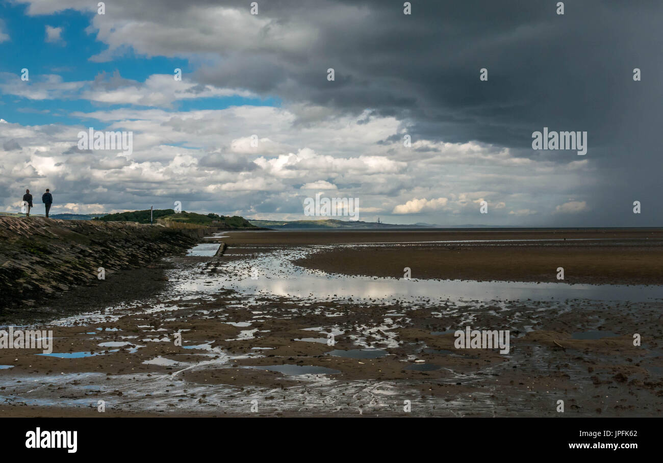 Sunny Summer weather and dramatic dark clouds with intermittent heavy showers over Firth of Forth tidal causeway, Cramond, Edinburgh, Scotland, UK - Stock Image