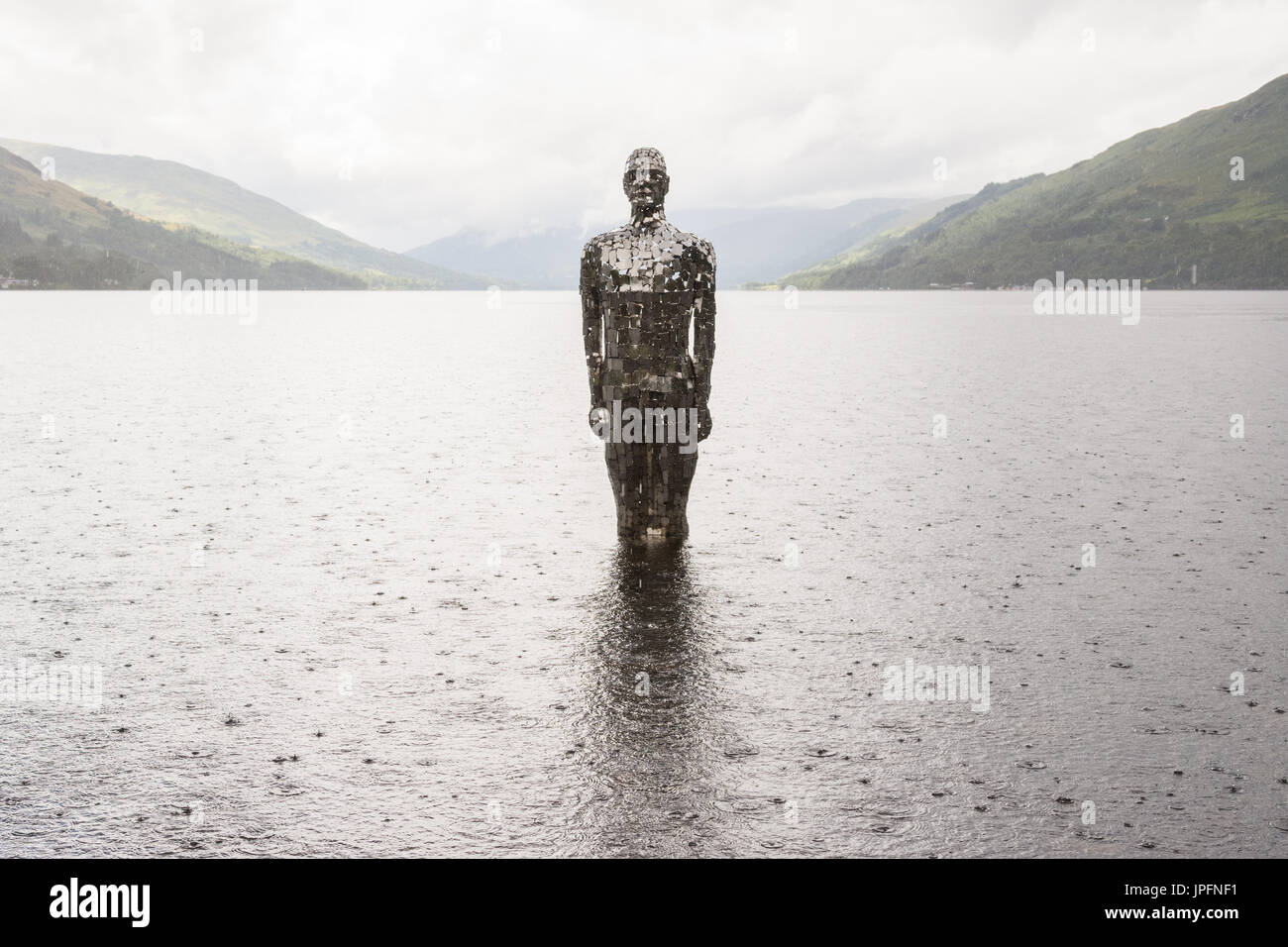 Loch Earn, St Fillans, Perth and Kinross, Scotland, UK. 1st Aug, 2017. UK weather - a looming figure titled 'Still', but locally known as Mirror Man endured a day of heavy showers with brief sunny intervals. The artwork by artist Rob Mullholland is made from mirrored tiles. Credit: Kay Roxby/Alamy Live News - Stock Image