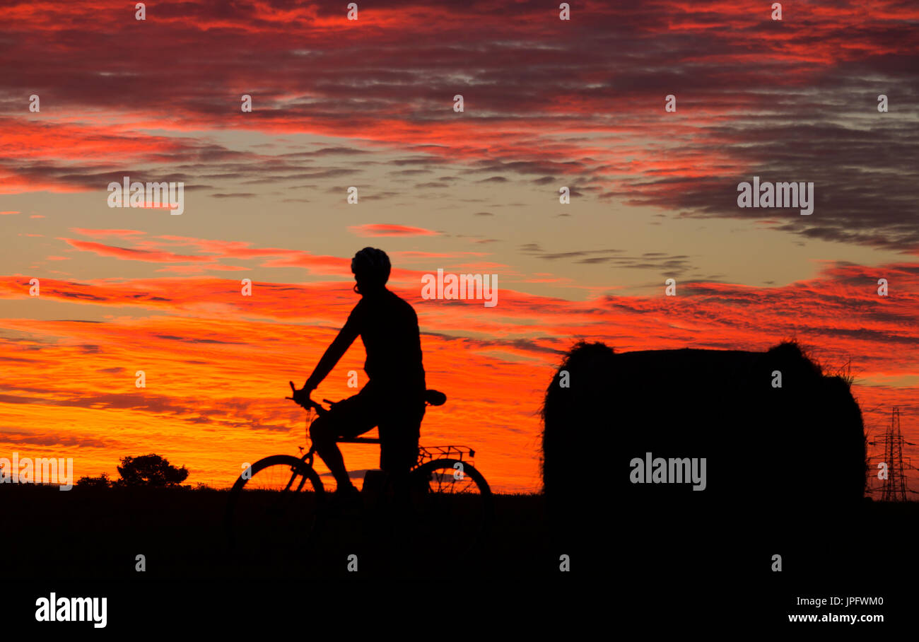 Billingham, north east England, UK, 2nd August, 2017. UK Weather: Shepherds warning sky. As a band of early morning rain sweeps across the south and west of the UK on Wednesday morning, it`s a glorious sunrise on the east coast, where the rain is not expected unitl mid afternoon. PICTURED: A mountain biker riding past hay bales at sunrise stops to watch a stunning sunrise unfold. Credit: ALAN DAWSON/Alamy Live News - Stock Image