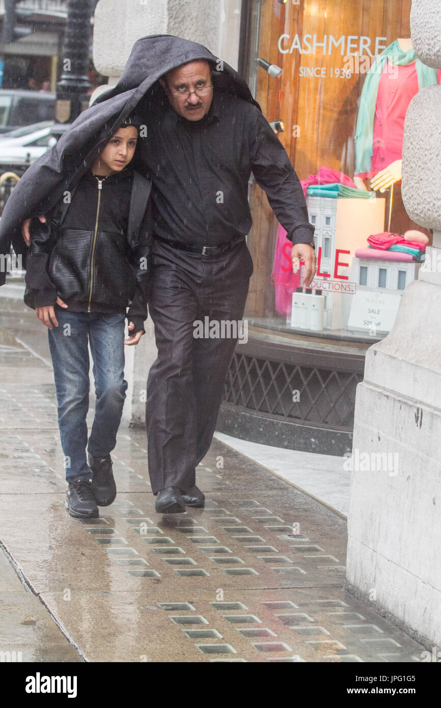 London, UK. 2nd Aug, 2017. UK Weather. Pedestrians in Piccadilly Circus, central London are caught in heavy rain Stock Photo