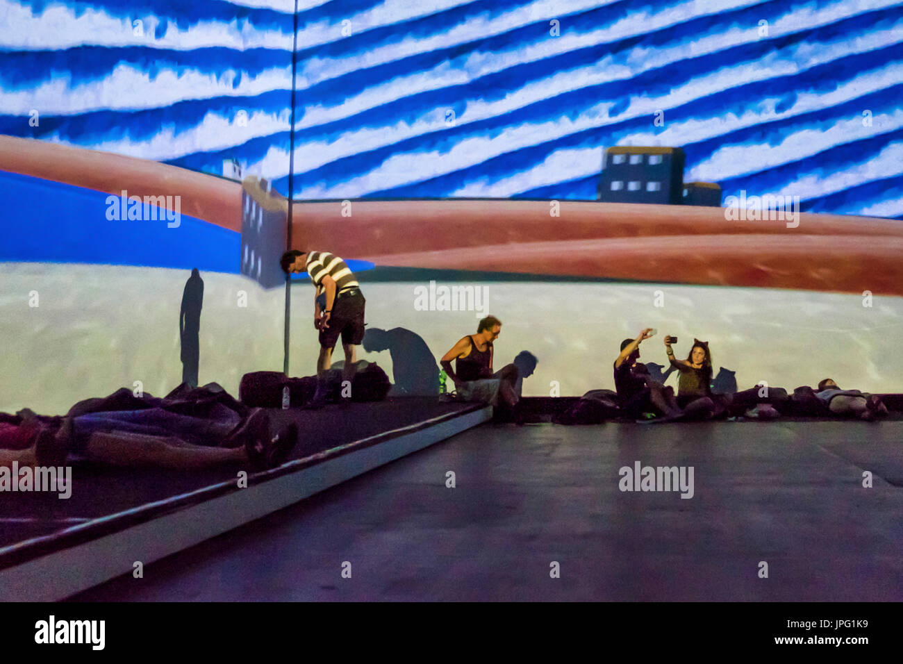 Berlin, Germany, 1st August 2017. People enjoy a multimedia video art show 'From Monet to Kandinsky.Visions Alive' . The exhibition presents the works of 16 Modernist artists on 7 meter screens placed at different angles in two viewing rooms. Credit: Eden Breitz/Alamy Live News - Stock Image