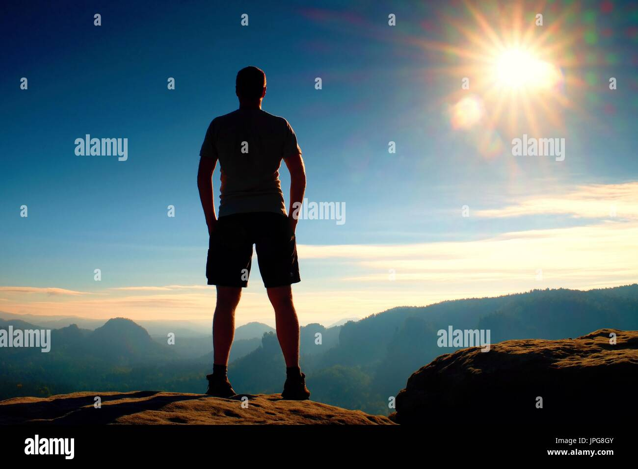 Alone hiker in black pants  stand on rock empire and watching over the misty and foggy morning valley to Sun. Beautiful Stock Photo