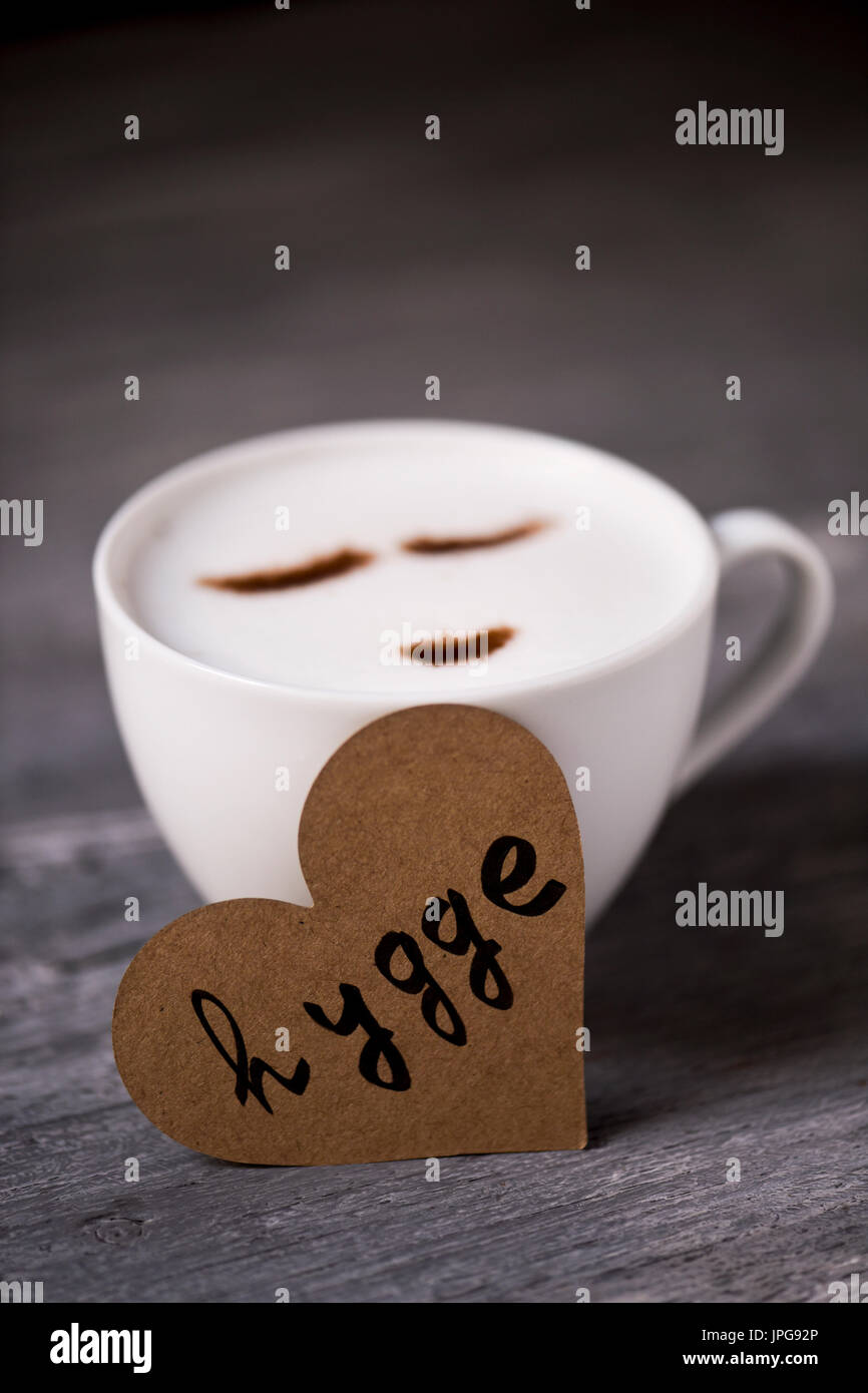closeup of a cup of cappuccino with a happy face drawn with cocoa powder and a heart-shaped signboard with the text hygge, a danish and norwegian word - Stock Image