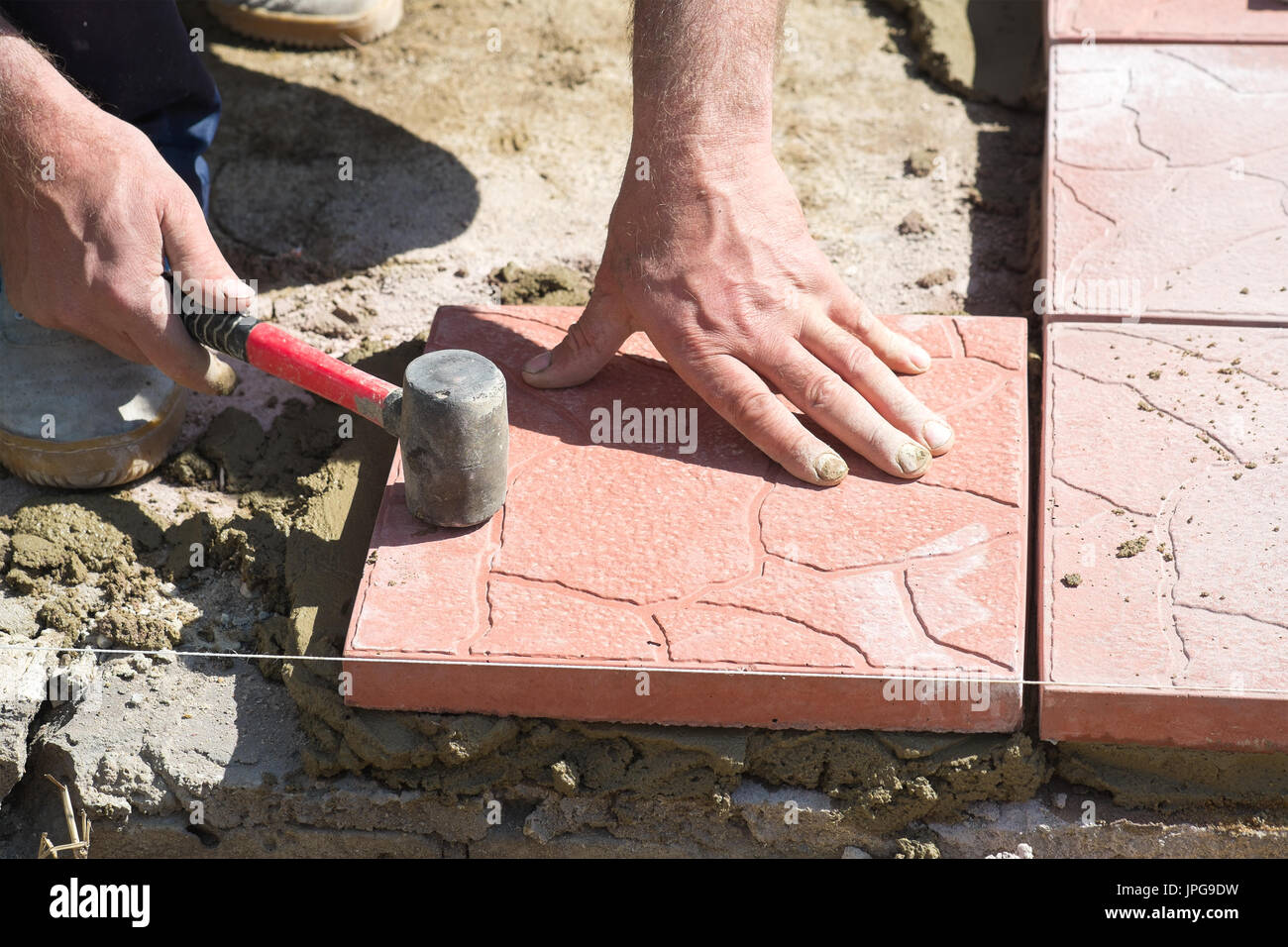 Installation of paving slabs - Stock Image