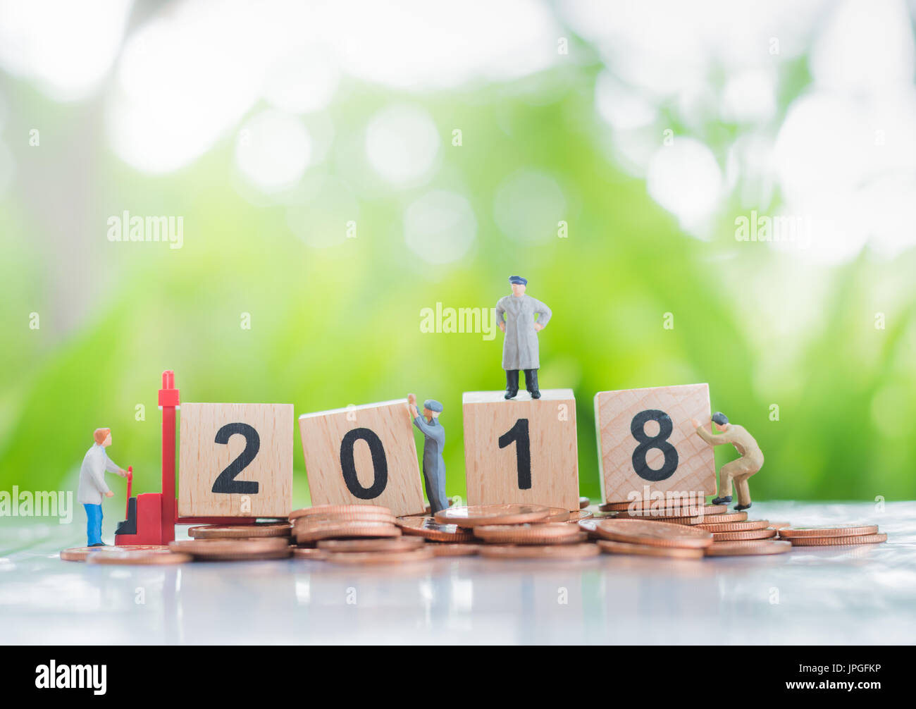 Tiny miniature model of working hard workers standing on a pile of coins and wooden number 2018 background using as investment, achievement and partne - Stock Image