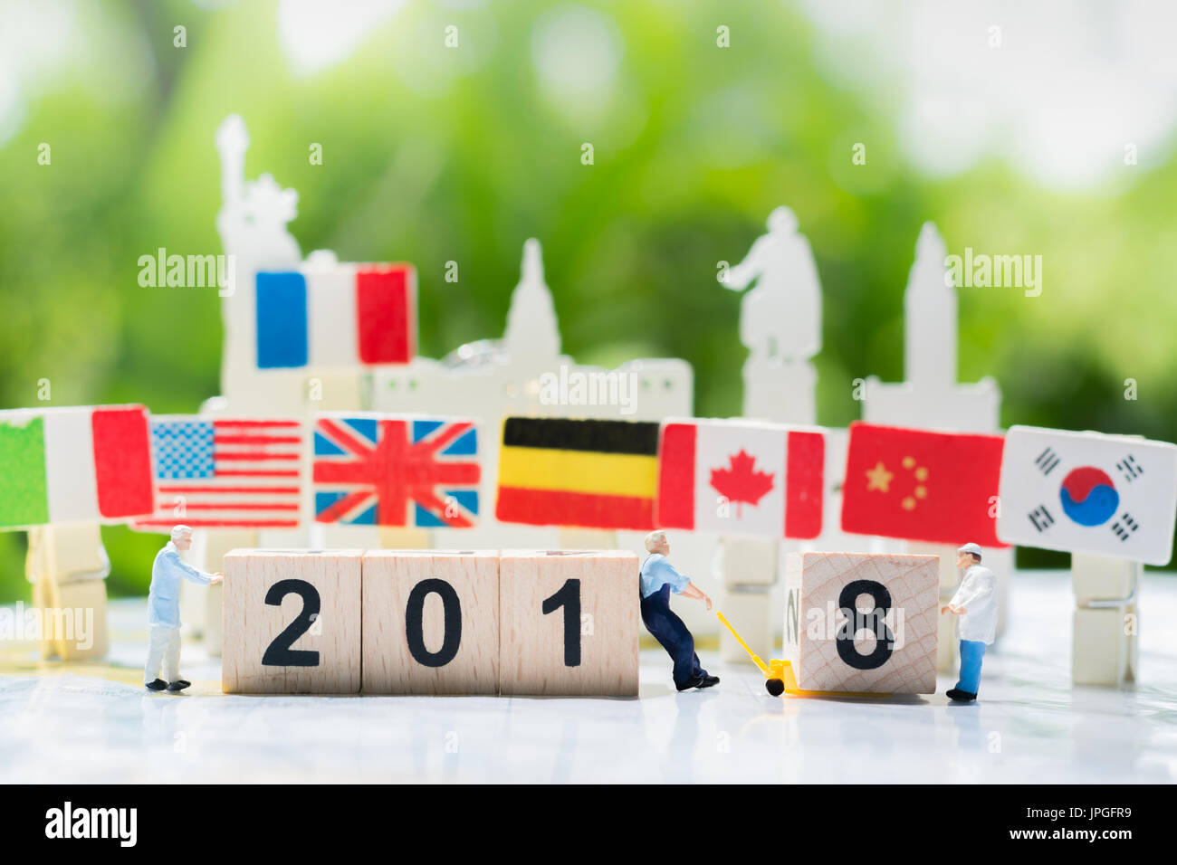 Workers are transfering or pulling a wooden number 8 to link with number 2018 with internation flags background using as happy new year 2018, teamwork - Stock Image