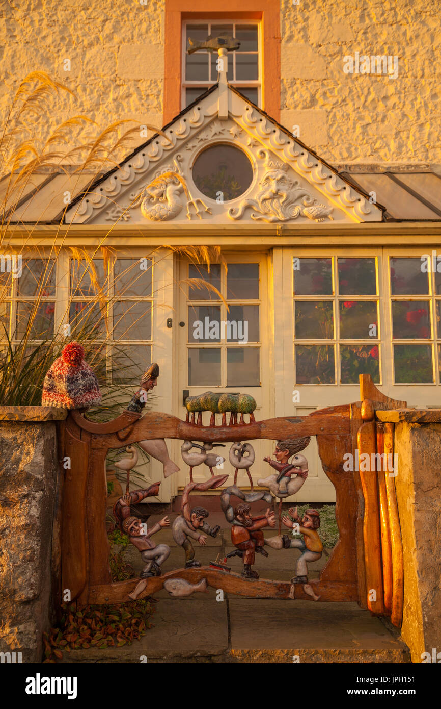 Handmade gate with carved figures on a house in Lower Largo, Fife, SCotland. - Stock Image