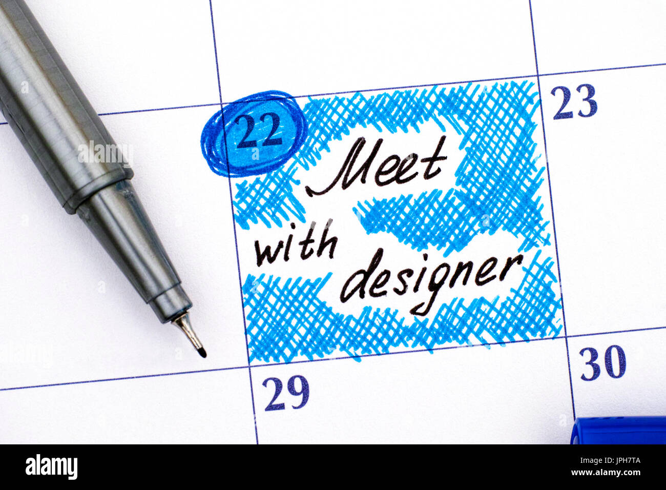 Reminder Meet with designer in calendar with blue pen. Close-up. - Stock Image