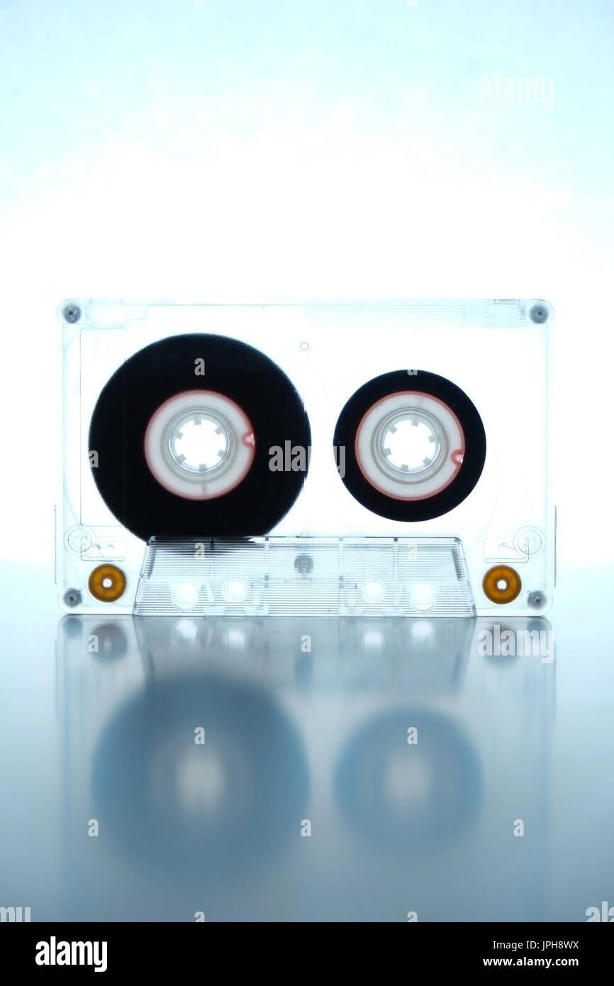 Old audio cassette being backlit on a white background. Retro and vintage theme - Stock Image