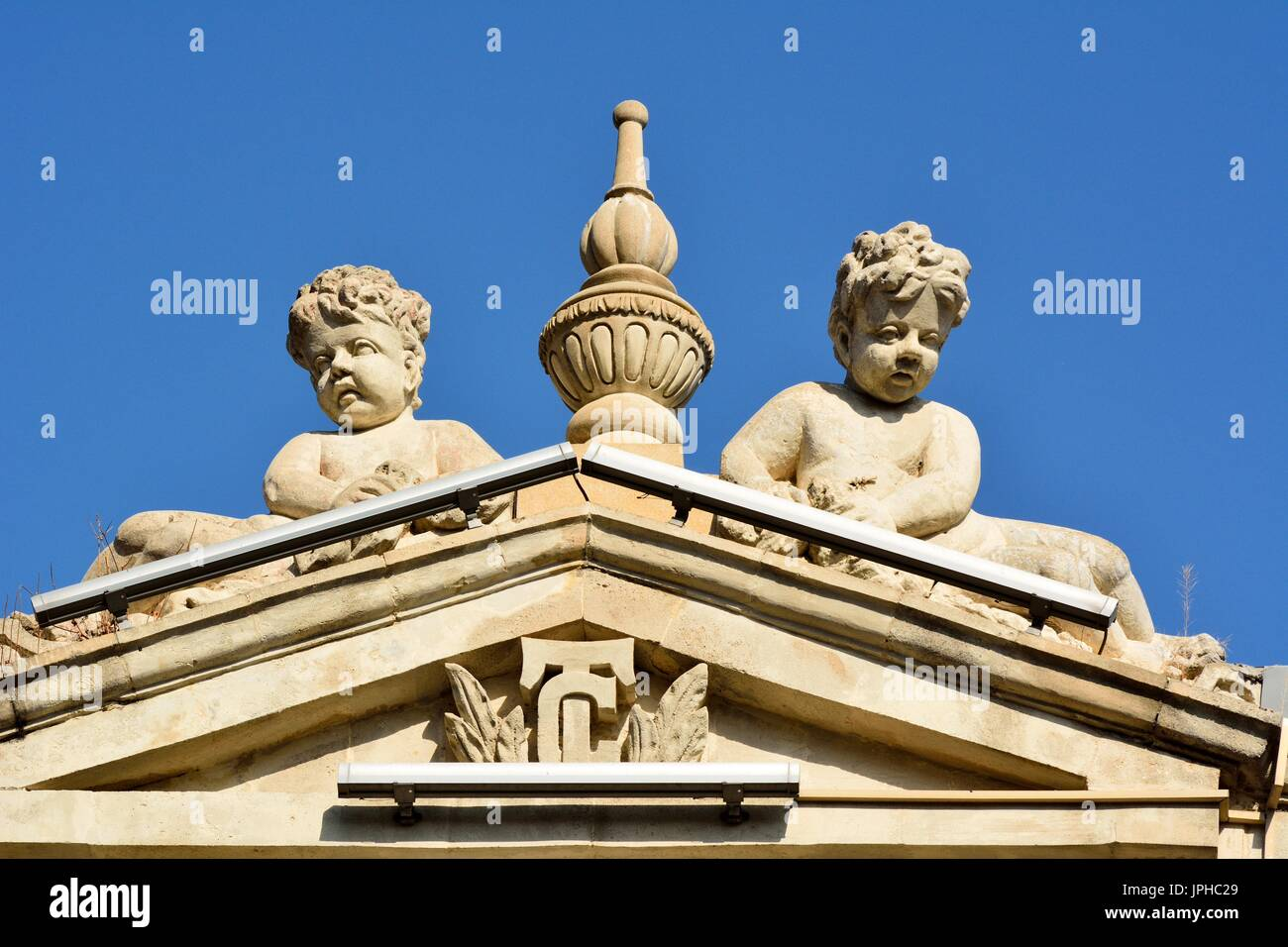 Sculptures of angel boys on facade of architectural building in downtown Baku. - Stock Image