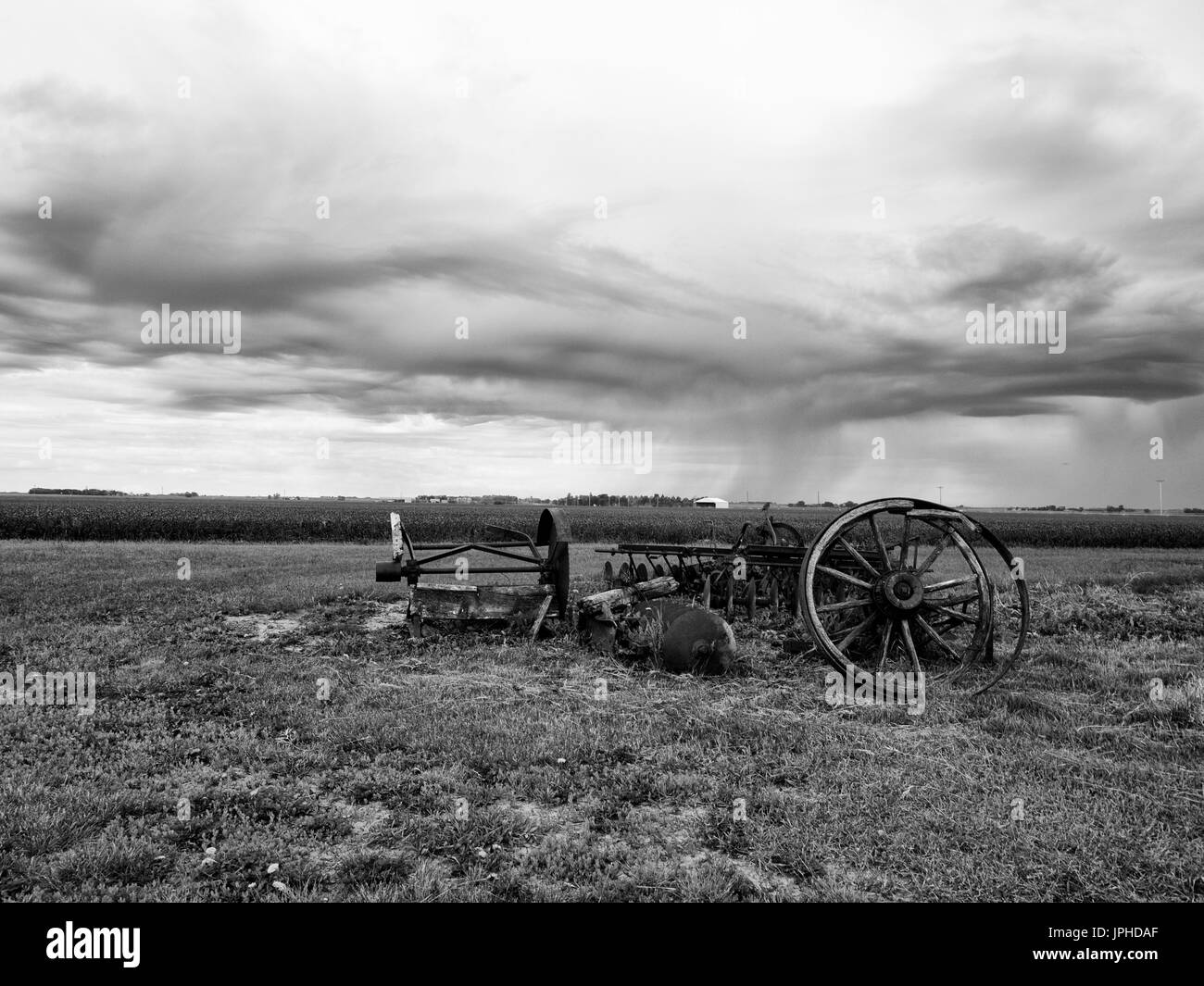 black and white Old Farm equipment scrap metal in the fields - Stock Image