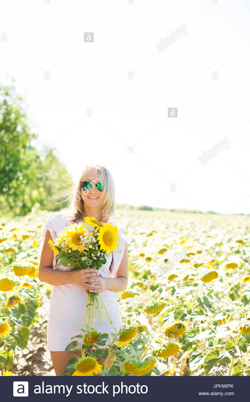 2a4b7e306e A blonde woman in a pink dress in a field with sunflowers. A woman holds