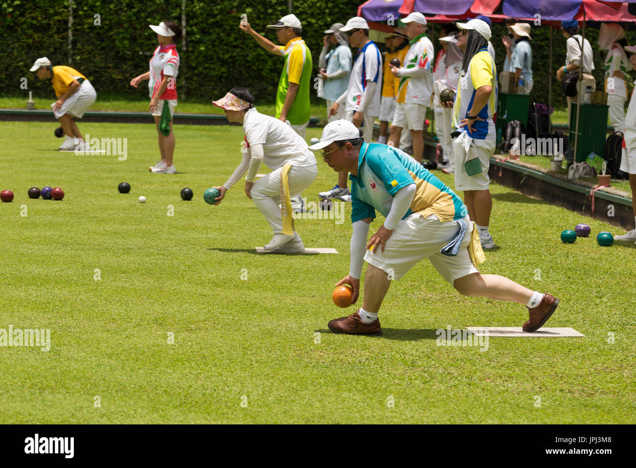 Chinese men and women competing at lawn bowling on a bowling green in Hong Kong - Stock Image