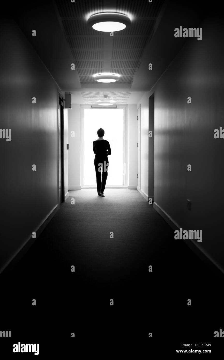 Woman, standing by a window at the end of a corridor, looking out, symbolic 'light at the end of the tunnel' living Stock Photo