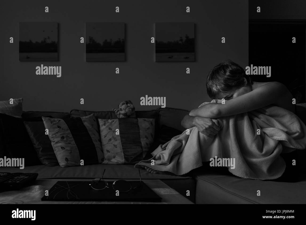 Depressed woman, curled up on sofa, clutching legs, showing what it feels like living with Depression and Anxiety. - Stock Image