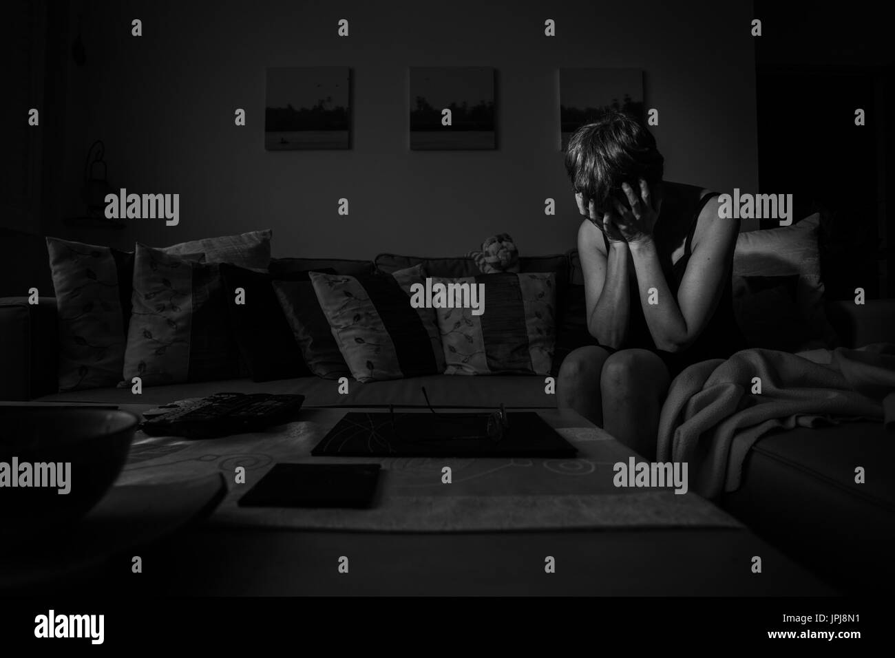 Depressed woman, head in hands, crying in despair, showing what it feels like living with Depression and Anxiety. Stock Photo