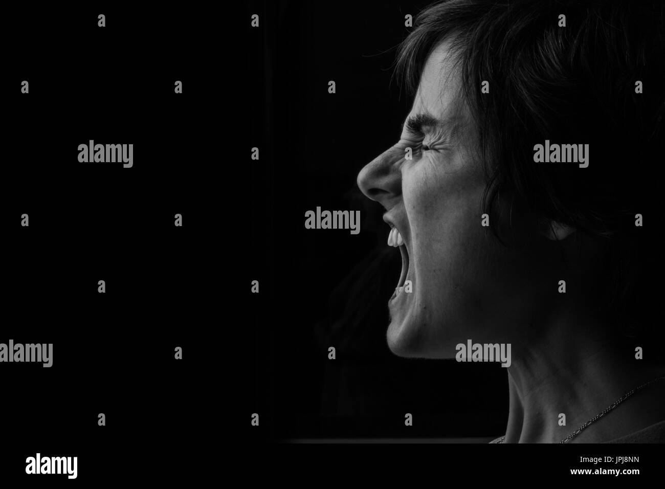 Depressed woman screaming to be heard, showing what it feels like living with Depression and Anxiety. - Stock Image