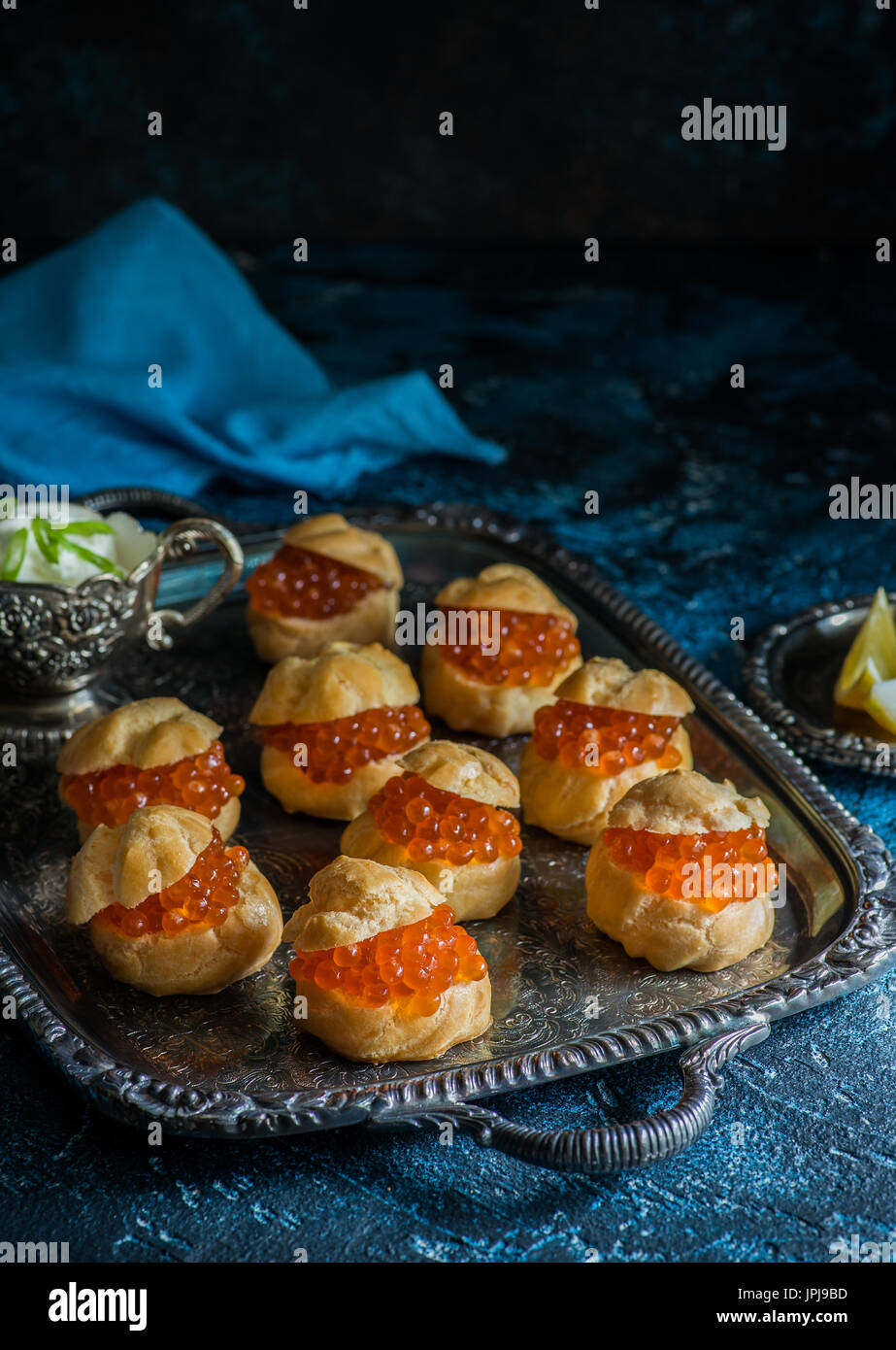 Homemade profiteroles stuffed with red caviar with sour cream on vintage tray over dark blue wooden background. Dark rustic style, natural light - Stock Image