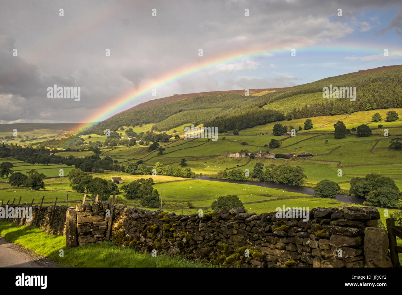 Rainbow over Simons Seat in Wharfedale, North Yorkshire, UK - Stock Image