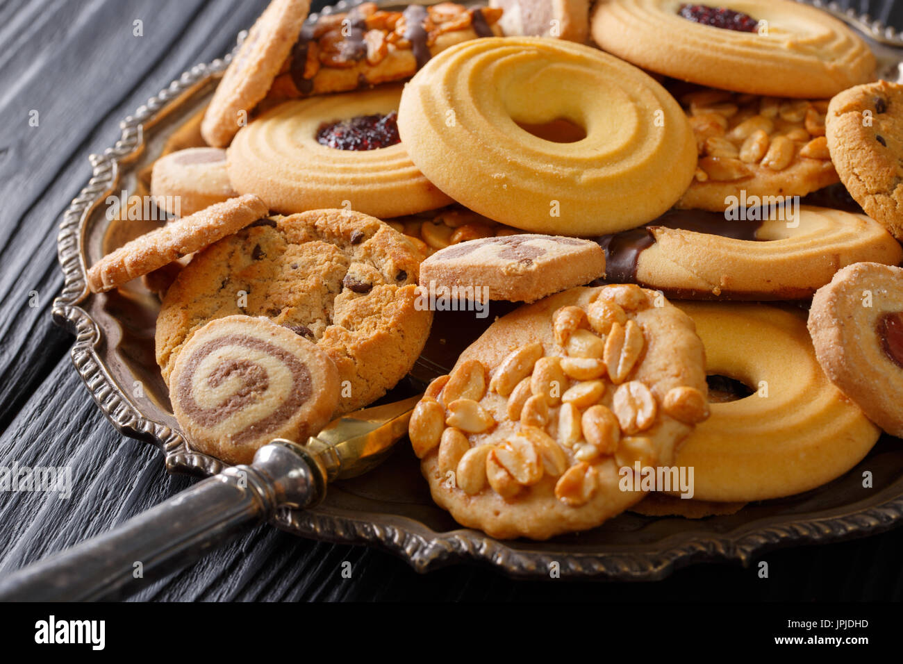 Mixed cookies with chocolate, jelly and nuts on the plate, selective focus. horizontal - Stock Image