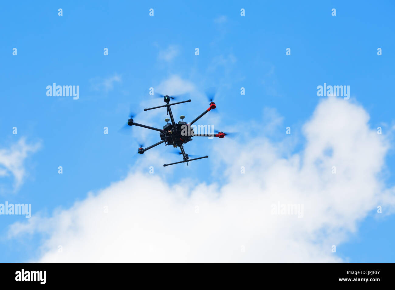 Flying hexacopter drone against a blue sky with clouds. - Stock Image