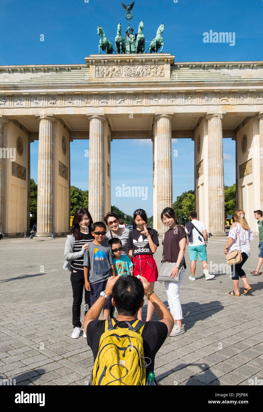 Asian tour group posting for photograph in front of Brandenburg Gate in Mitte district of Berlin Germany Stock Photo