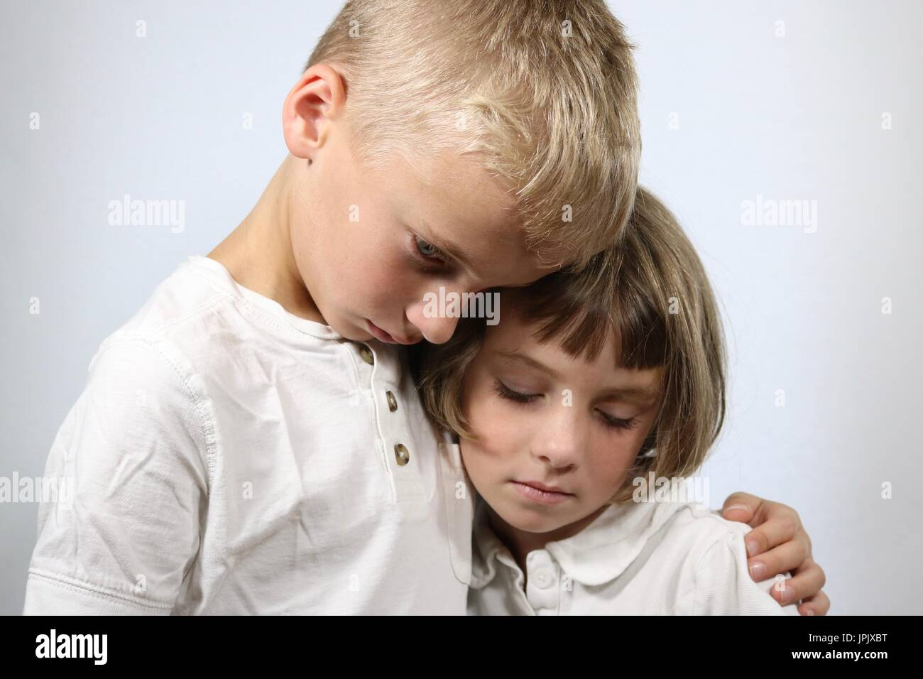 Portrait of grieving young children in an embrace - Stock Image