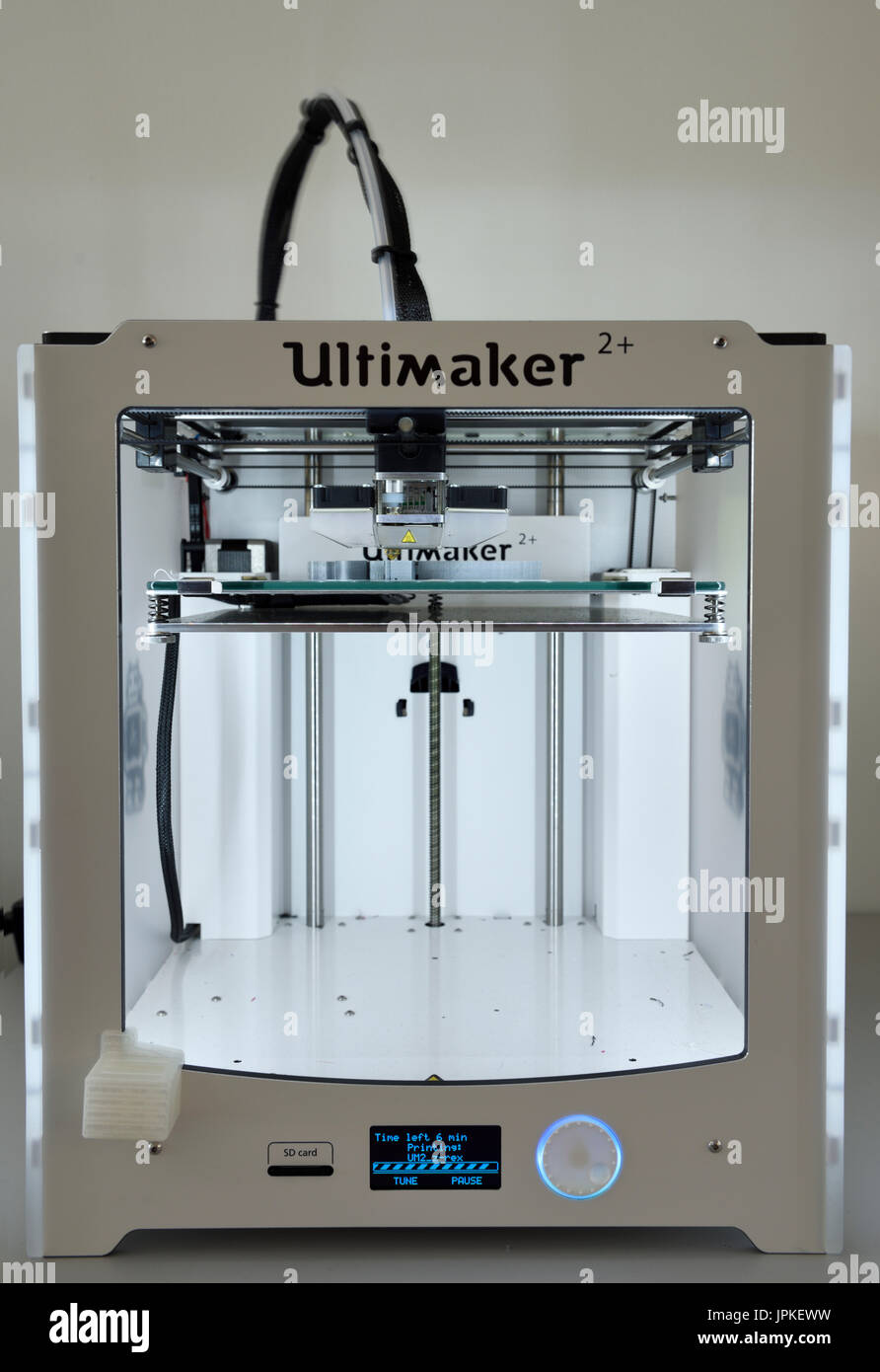 Front of a 3D three dimensional printer extruding Polylactic acid PLA polymer to print a plastic object - Stock Image