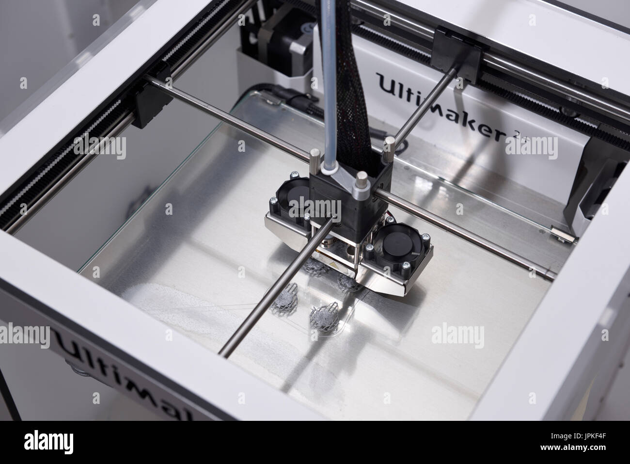 Top of a 3D three dimensional printer extruding Polylactic acid PLA polymer to print plastic objects showing the extrusion nozzle head - Stock Image