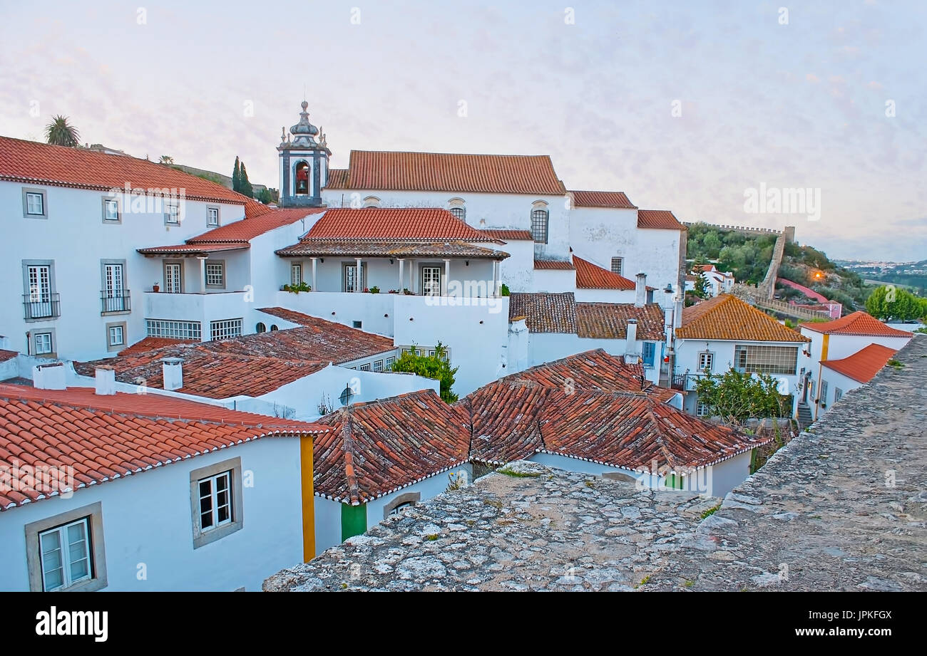 The St James Church dominates over the tile roofs of old Obidos, surrounded by preserved ramparts, Portugal. - Stock Image