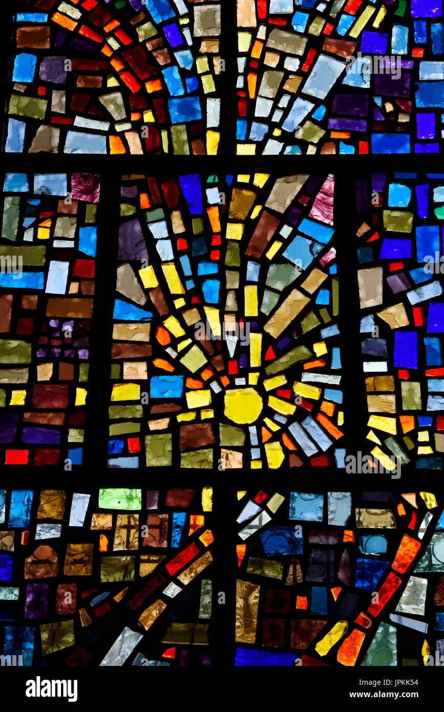 Abstract sun pattern of colors in a stained glass window mosaic in a Toronto Roman Catholic church - Stock Image