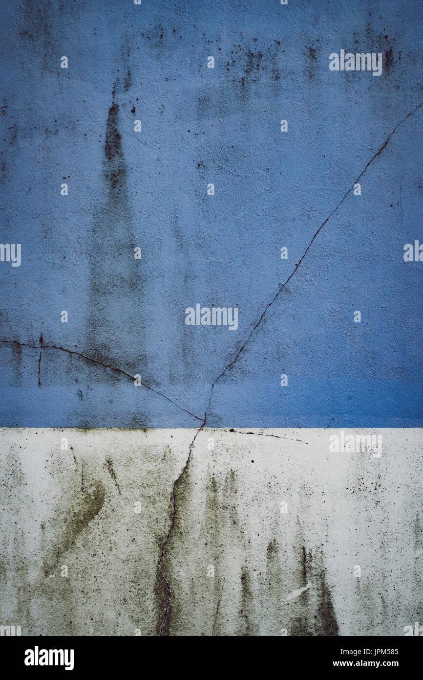 Cracked and grimy two-tone painted wall in Hove, East Sussex. - Stock Image