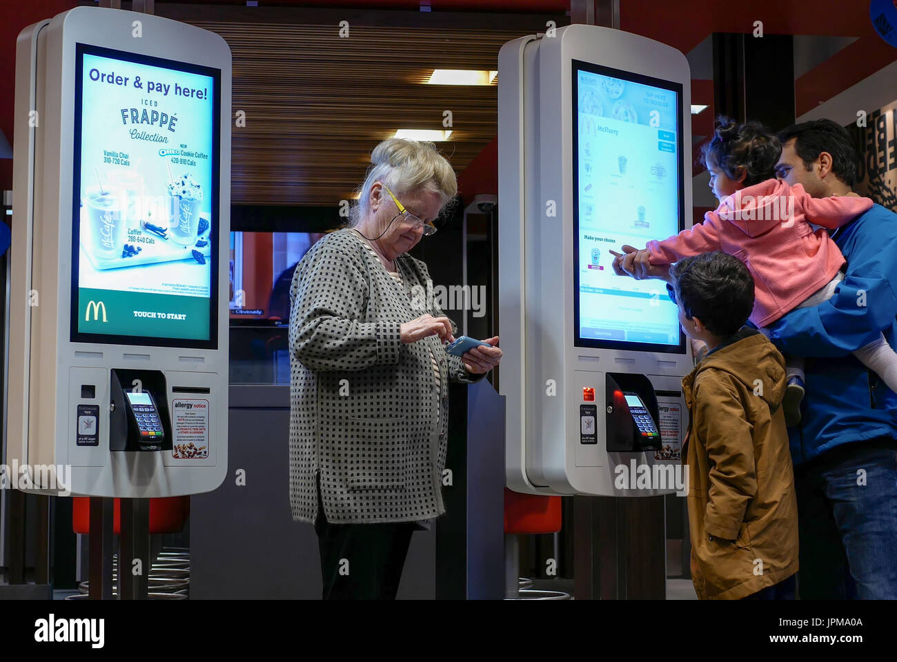 Coquitlam, BC, Canada - April 11, 2017 : Family ordering food at self check out machine and old lady playing cellphone at Mcdonalds restaurant - Stock Image