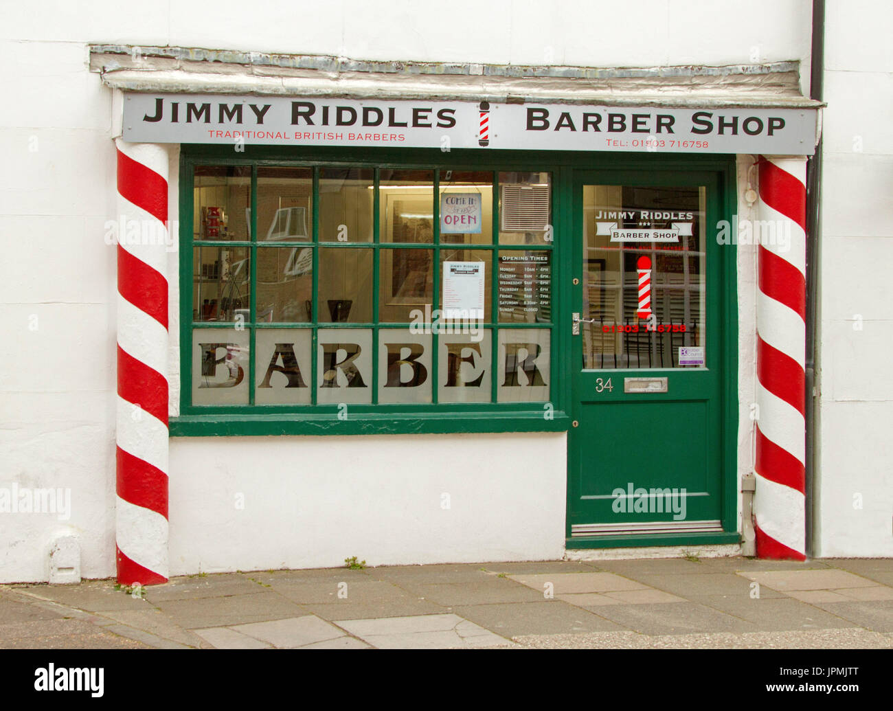 Exterior of Jimmy Riddles Barber's shop with red and white striped barber's pole, green door, and white wall, in Littlehampton, England - Stock Image