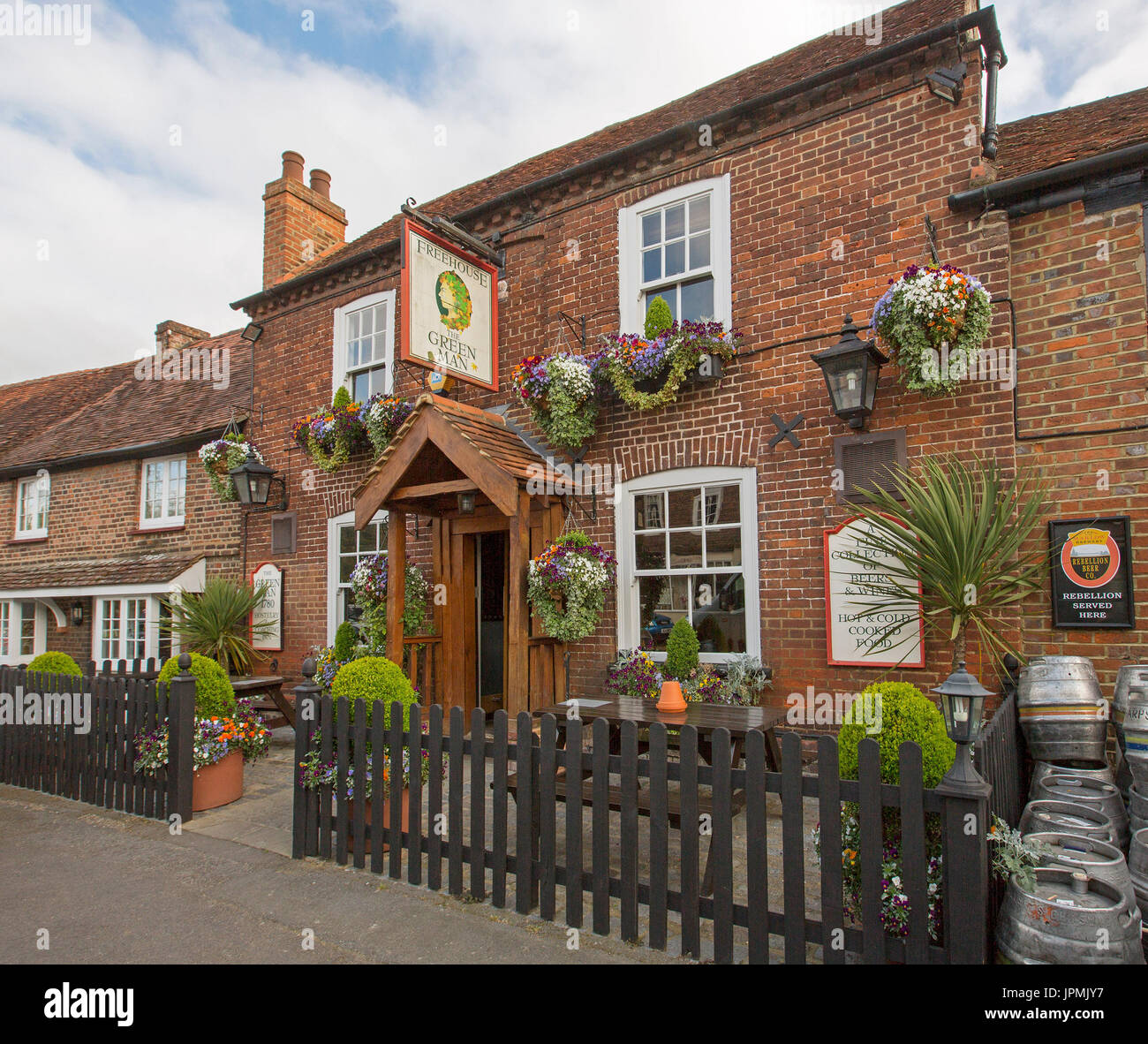 Red brick pub, The Green Man, a free house with hanging baskets of flowers, picket fence, and beer kegs in English village of Denham - Stock Image