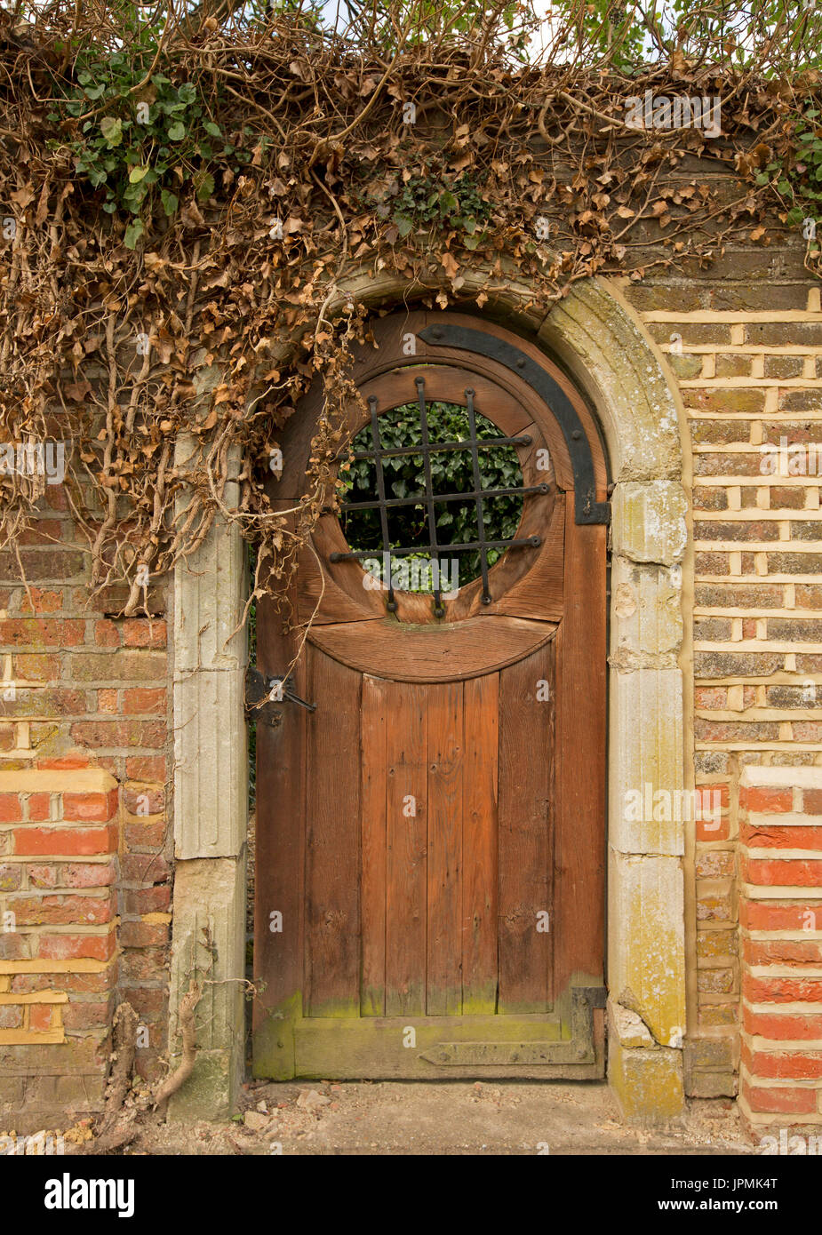 Unusual Arched Reddish Brown Wooden Door With Circular Grill U0026 Unique  Artistic Hinges In Red Brick Wall, Entrance To Garden In English Village