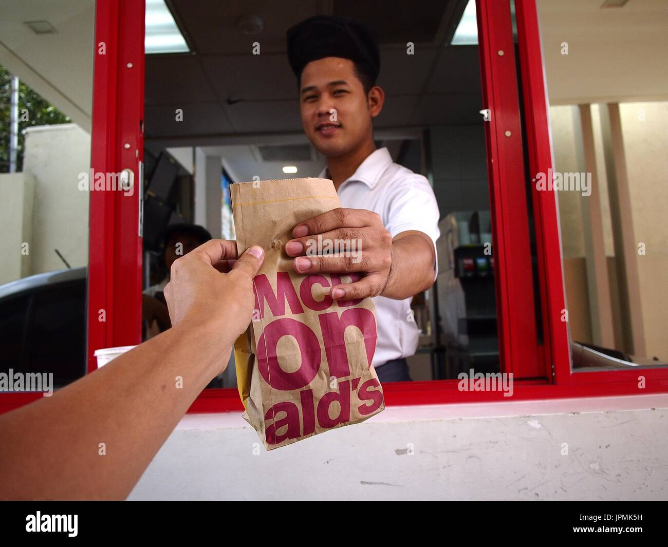 ANGONO, RIZAL, PHILIPPINES - JULY 29, 2017: A fast food chain worker hands over an order of food to a customer at a drive thru counter. - Stock Image