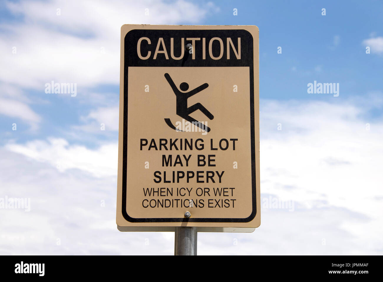 Caution, Slippery when wet sign in a parking lot. Warning patrons. Blue sky with fluffy white clouds in background - Stock Image