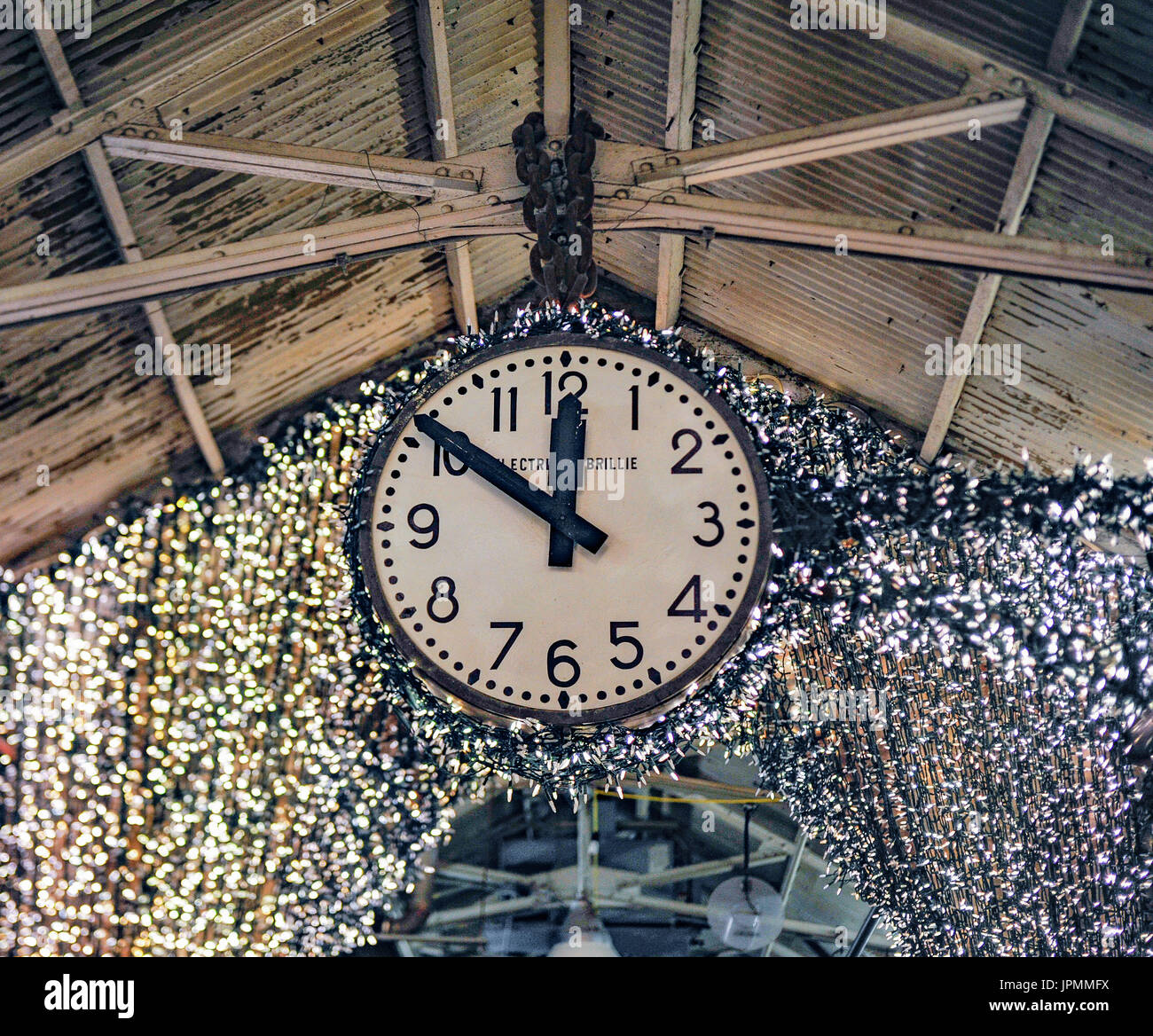 An Electrique Brillie clock hanging from the rafters at Chelsea Market, in Manhattan, NYC - Stock Image