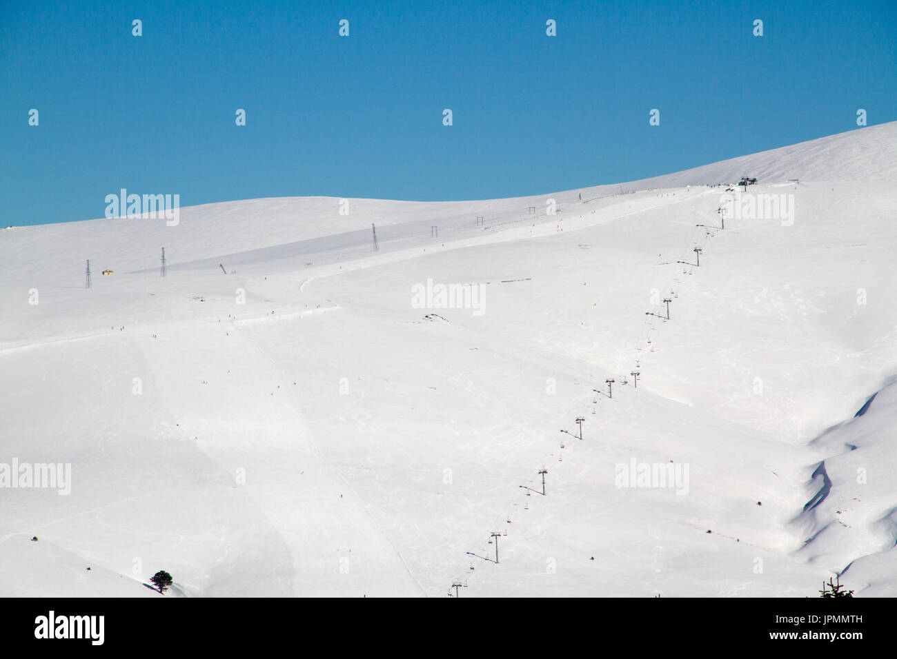 Ski tracks on the background of snowy mountains and blue sky - Stock Image