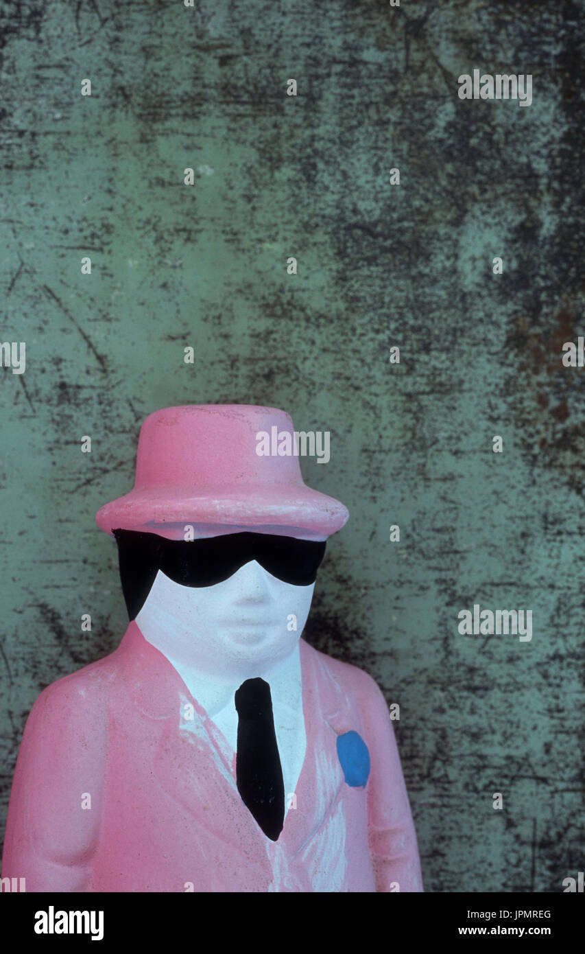 Model of shifty gangland or mafia member in dark glasses and pink jacket and hat standing in front of battered green wall - Stock Image