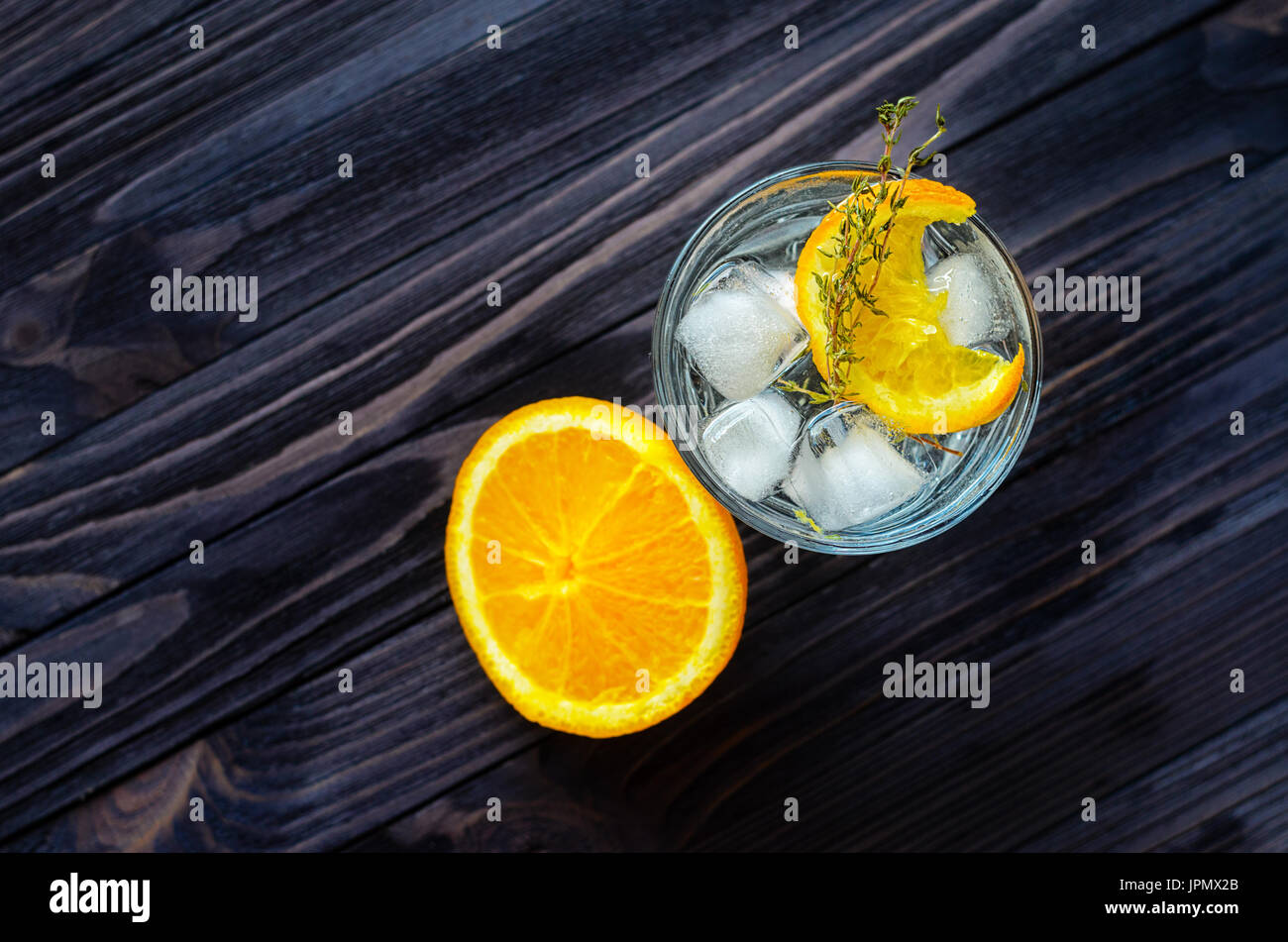 Cut orange near the alcoholic cocktail on dark wood table top view. Blank space for text placement - Stock Image