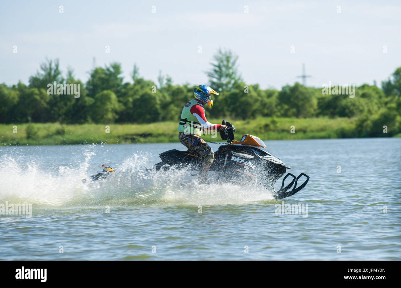man on snowmobile goes fast on the water in summer - Stock Image