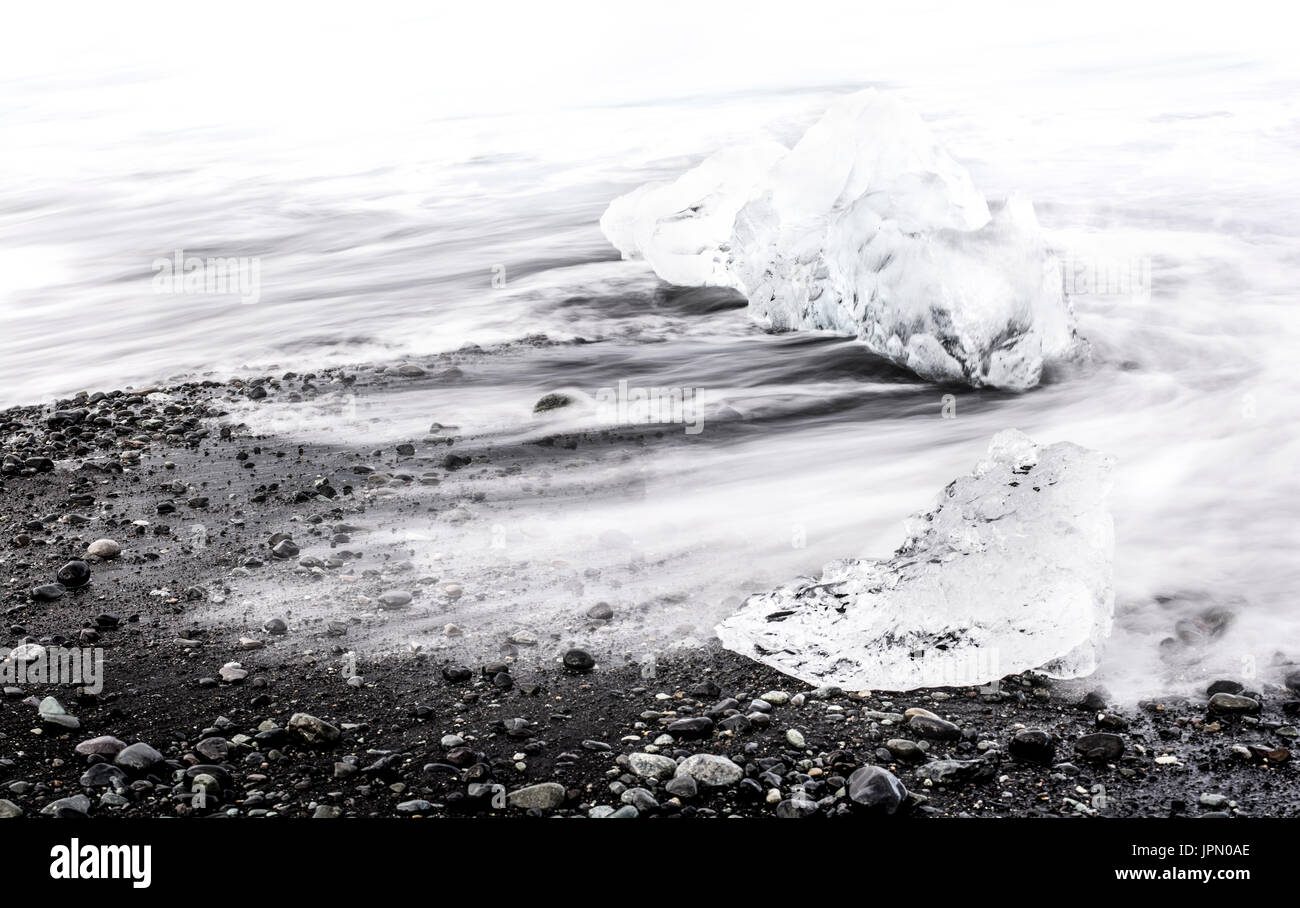 Long exposure shot of blocks of ice from the glacier in the sea off Iceland - Stock Image
