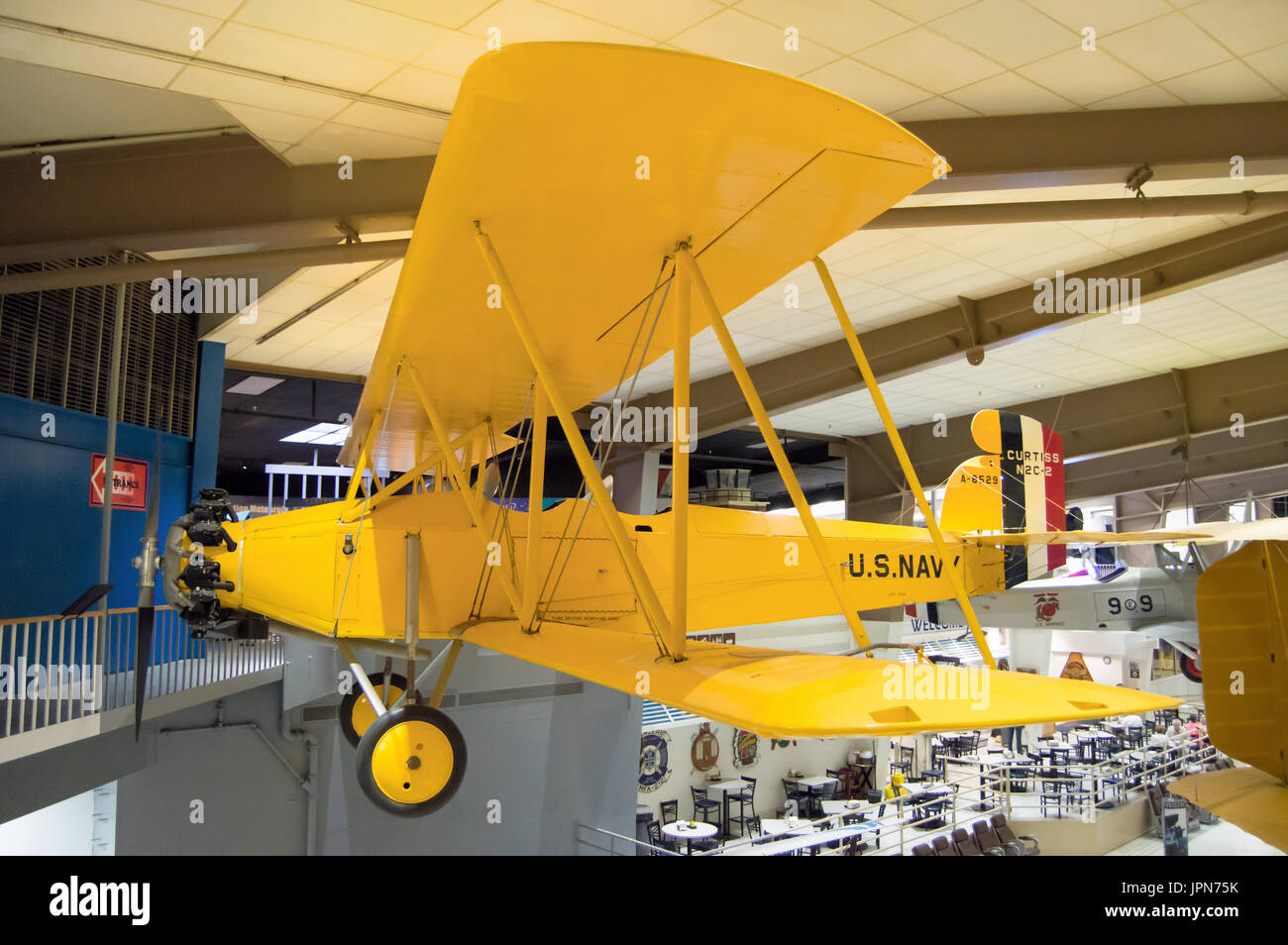 A yellow bi-plane on display at the national museum of naval aviation. - Stock Image